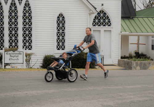 Father Running with His Son in a Stroller in the Second Chance Mission Run 5k